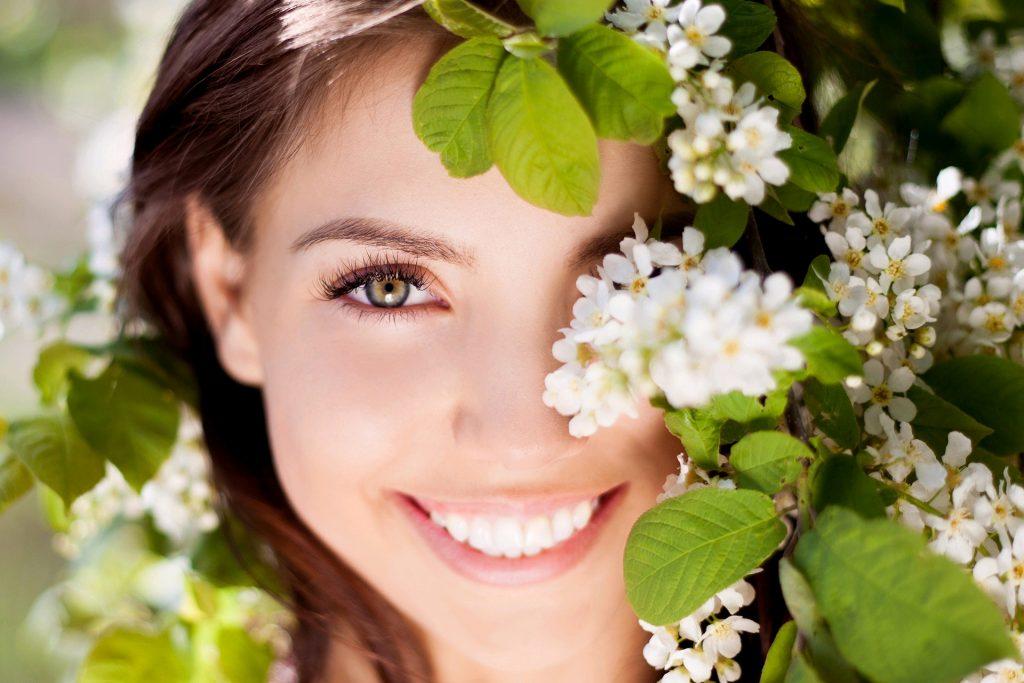 лицо улыбающейся женщина в цветах яблони